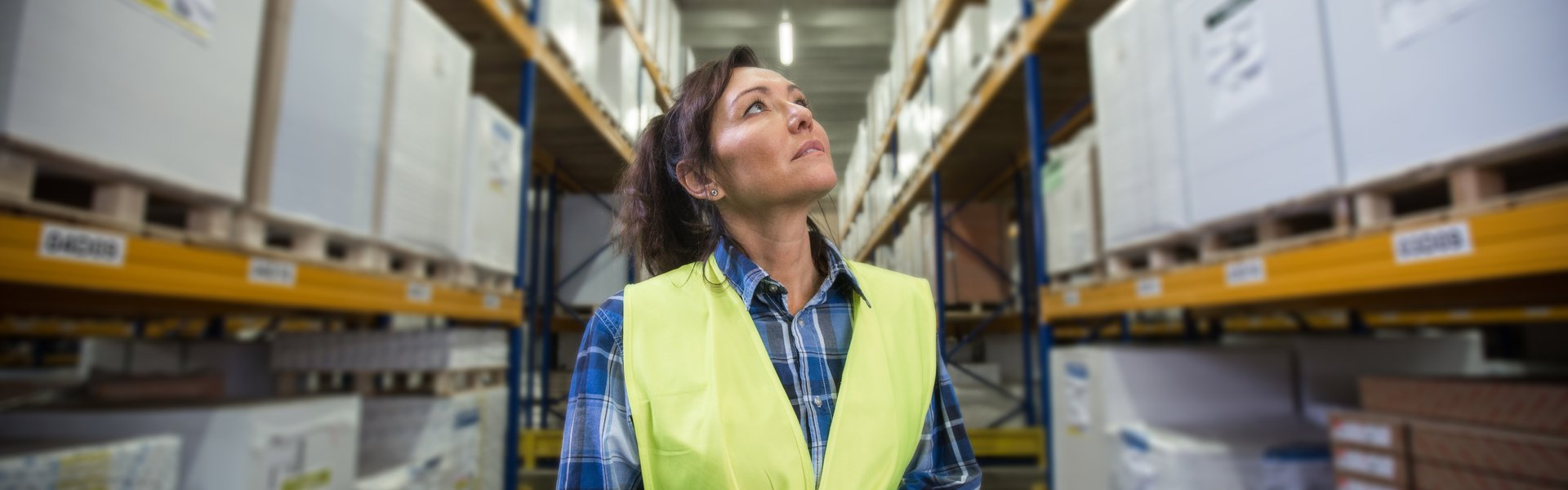 Puzzled woman in warehouse working with hand scanner and looking for one particular item. First in first out, Last in last out, team working together concept photo. p738