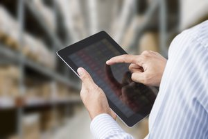 Businessman checking inventory in stock room on tablet p698